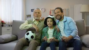 Granddad, dad and preteen son cheering for national football team at home, hobby. Stock footage stock video