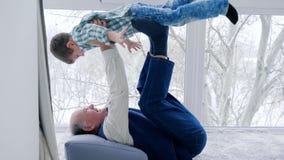 Granddad fool around with grandchildren lying on floor at home