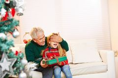 Granddad holding eyes of child closed. While offering a gift at christmas royalty free stock photos