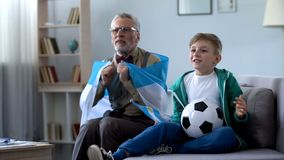 Granddad wrapped in Argentina flag watching soccer with boy, worrying about game. Stock photo stock photos