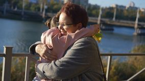 Granddaughter with a bouquet of yellow autumn leaves ran up to her grandmother and hugging her in a Park by the river.