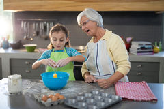 Granddaughter breaking eggs and grandmother watching Royalty Free Stock Photography