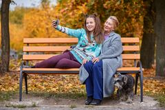 Granddaughter makes selfie with grandmother with a slight smile in the autumn park Stock Photo