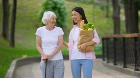 Granddaughter bringing food to elderly female patient, walking in hospital park. Stock footage stock footage