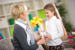 Granddaughter bringing yellow flowers to her grandmother Royalty Free Stock Photos