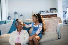 Granddaughter brushing her grandmothers hair in living room Stock Image