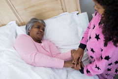 Granddaughter comforting sick grandmother in bed room Stock Photography