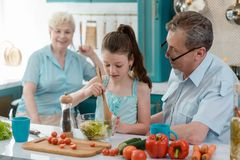Granddaughter cooking salad. For her grandparents. Happy family in the kitchen, healthy eating concept royalty free stock photo