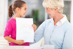Granddaughter drawing granny Stock Photo