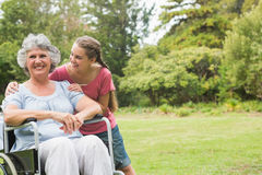 Granddaughter embracing grandmother in wheelchair. In the park on sunny day Royalty Free Stock Photo