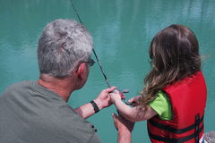 Granddaughter fishing with Grandpa. Royalty Free Stock Image