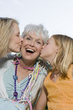 Granddaughter And Friend Kissing Woman Stock Image