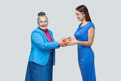 Granddaughter gives a gift to a funny old grandmother. Granddaughter in blue dress smiles and gives a gift to her lovely grandmother, looking at camera with stock photos