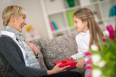 Granddaughter giving gift to her grandmother. Surprise for sweetheart grandma stock photo