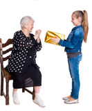 Granddaughter giving gift to her grandmother. On a white background stock photography