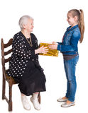 Granddaughter giving gift to her grandmother. On a white background royalty free stock image