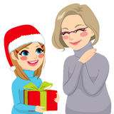 Granddaughter Giving Present To Grandmother. Happy granddaughter in Christmas day giving present to lovely grandmother Royalty Free Stock Photo