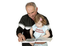 Granddaughter grandfather reading a book Royalty Free Stock Photo