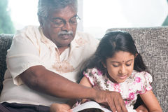 Granddaughter and grandfather reading book royalty free stock photo