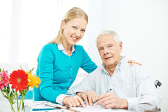Granddaughter and grandfather solving crossword puzzle Stock Photo