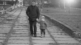 Granddaughter and grandfather walking in the city park holding hands. Black and white. Slow motion