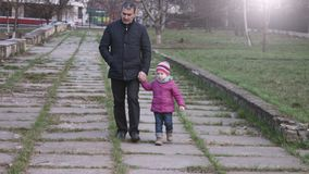 Granddaughter and grandfather walking in the city park holding hands. Slow motion
