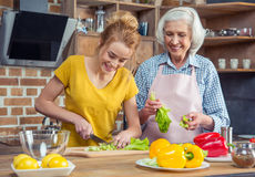 Granddaughter and grandmother cooking together Stock Photo