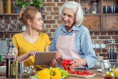 Granddaughter and grandmother cooking together Stock Images