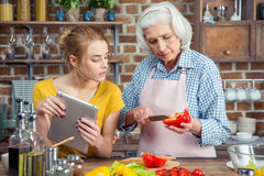 Granddaughter and grandmother cooking together Royalty Free Stock Image