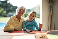 Granddaughter and grandmother drawing in the deck shade near the pool Royalty Free Stock Image