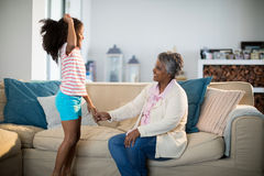 Granddaughter and grandmother having fun in living room Stock Photo