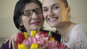Granddaughter with grandmother holding flowers and smiling on camera. Slowly
