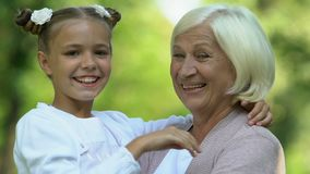 Granddaughter and grandmother hugging and showing thumbs-up gesture, good sign stock video