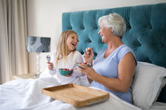 Granddaughter and grandmother interacting while having breakfast Stock Images