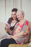 Granddaughter and grandmother looking at mobile phone Stock Image