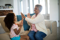 Granddaughter and grandmother playing clapping games on sofa in living room Royalty Free Stock Photo