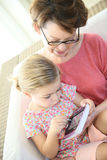 Granddaughter and grandmother playing on a tablet royalty free stock image