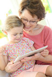 Granddaughter and grandmother playing together on a tablet stock photos
