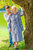 Granddaughter and grandmother posing in a park Stock Image