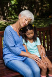 Granddaughter and grandmother sleeping while sitting on wooden bench Royalty Free Stock Photo