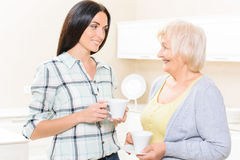 Granddaughter and grandmother standing with cups Stock Photography