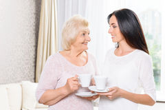 Granddaughter and grandmother standing with cups Royalty Free Stock Photos