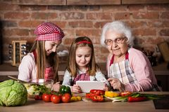 Granddaughter and grandmother with tablet searching recipe. To cook healthy vegetarian salad Stock Photography