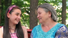 Granddaughter and grandmother talking and laughing stock footage