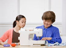 Granddaughter and grandmother use sewing machine Royalty Free Stock Photo