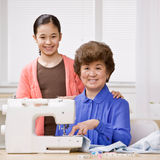 Granddaughter and grandmother use sewing machine Stock Photos