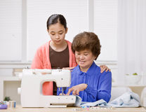 Granddaughter and grandmother use sewing machine Royalty Free Stock Image