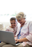 Granddaughter and grandmother using laptop Royalty Free Stock Images