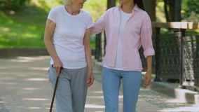 Granddaughter and grandmother with walking stick relaxing in park, togetherness. Stock footage stock video