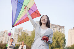 Granddaughter and grandparents with kite in the park Royalty Free Stock Image